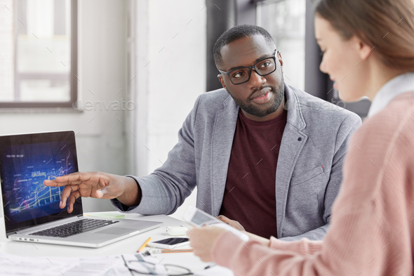 Serious black African American male tries to explain his female trainee startegy of development sale - Stock Photo - Images