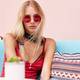 Blonde female with serious look wears red sunglasses, tank top, and bandana on neck, poses in cozy r - PhotoDune Item for Sale