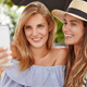 Photo of adorable young woman with light hair spends free time in company of her best friend, holds - PhotoDune Item for Sale