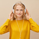 Closeup portrait of young woman looking to camera listening music via headphones on beige wall - PhotoDune Item for Sale