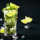 Mojito cocktail or mocktail with lime, mint, and ice in glass on blue background - PhotoDune Item for Sale