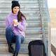 Woman in her twenties taking a coffee break sitting on some steps in the street - PhotoDune Item for Sale