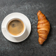 Cup of coffee and fresh croissant on black table - PhotoDune Item for Sale