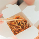 Wok noodles in takeaway box. Woman eating shrimps with chopsticks, close up view on female hands. - PhotoDune Item for Sale