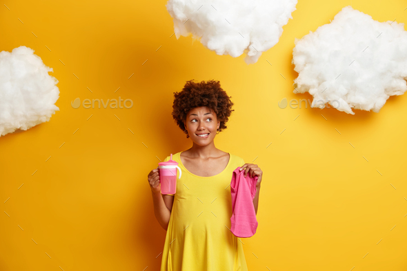 Pensive pregnant young Afro American woman dreams about child and future life holds feeding bottle a - Stock Photo - Images