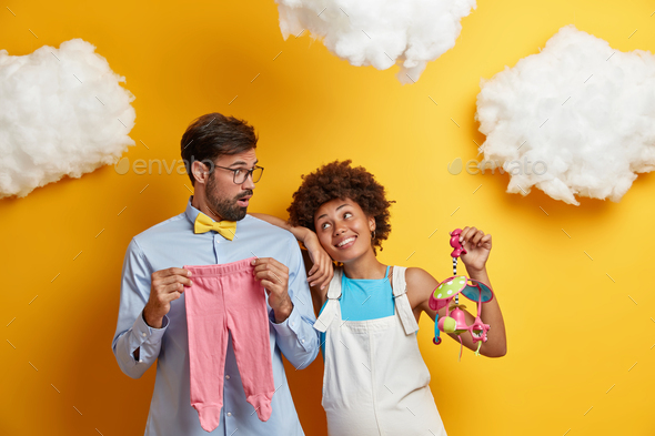 Husband and wife pose with baby items prepare for becoming parents. Cheerful pregnant woman holds mo - Stock Photo - Images