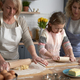 Three generations of women rolling dough together at home - PhotoDune Item for Sale