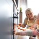 Girl and grandmother watching easter biscuits in kitchen oven - PhotoDune Item for Sale