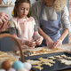Little girl making Easter cookies with family at home - PhotoDune Item for Sale