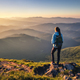 Girl on mountain peak looking at beautiful mountains at sunset - PhotoDune Item for Sale