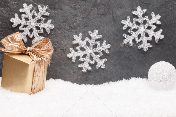 Christmas greeting card. Noel festive background. New year symbol. Gold gift box on snow. - Stock Photo - Images