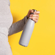 Woman in grey tee holding grey insulated bottle on yellow background - PhotoDune Item for Sale