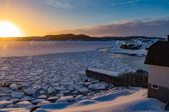 Winter sun sets over frozen ocean bay NL Canada - Stock Photo - Images