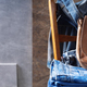 Denim jeans and old leather bag at wooden chair near grey wall background texture - PhotoDune Item for Sale