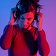 Attractive woman with headphones listening music in studio with blue and red lights - PhotoDune Item for Sale