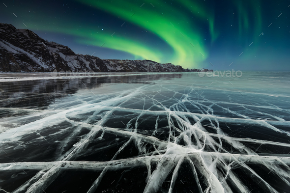 Aurora borealis over a rock in a frozen lake - Stock Photo - Images
