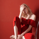 Beautiful young adult woman wearing red jumpsuit relaxing on chair - PhotoDune Item for Sale