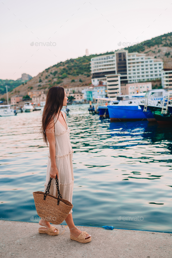 Young beautiful woman walking on dock near the boat - Stock Photo - Images