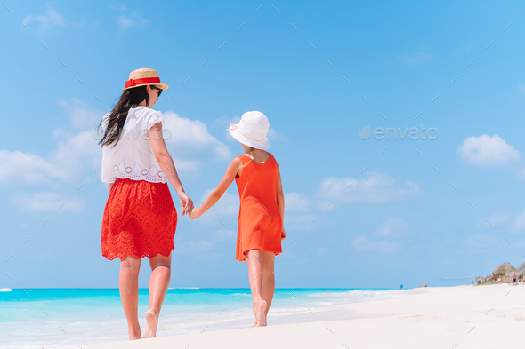 Beautiful mother and daughter at the beach enjoying summer vacation - Stock Photo - Images