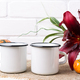 Two white campfire enamel mug mockup with pumpkin and lily - PhotoDune Item for Sale