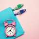 Toothbrush and alarm clock on pink background - PhotoDune Item for Sale