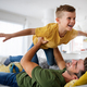 Cheerful young boy having fun with father together at home - PhotoDune Item for Sale