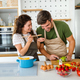 Happy young couple have fun in kitchen while preparing healthy organic food - PhotoDune Item for Sale