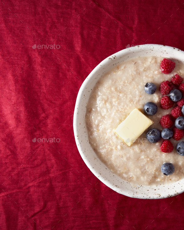 Part of oatmeal porridge with blueberry, bilberry. Close up breakfast in white bowl with fresh - Stock Photo - Images