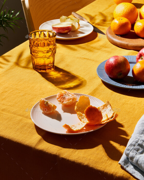 Food, breakfast with fruit. Table covering bright yellow linen tablecloth, sunlight deep hard shadow - Stock Photo - Images