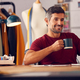 Mature Male Fashion Designer In Studio Sitting At Desk With Cup Of Coffee Working On Laptop - PhotoDune Item for Sale