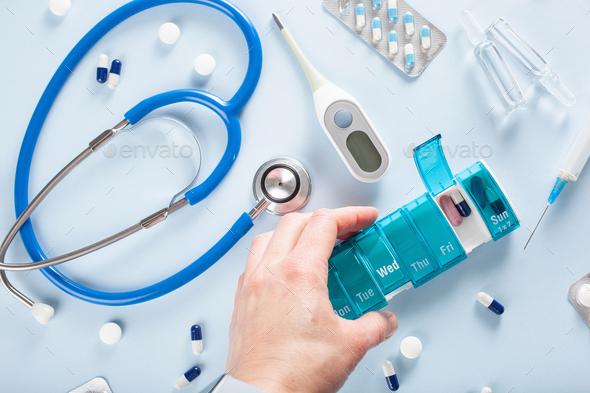 hand holding pill box, stethoscope syringe capsule medicine. medical treatment for flu virus - Stock Photo - Images