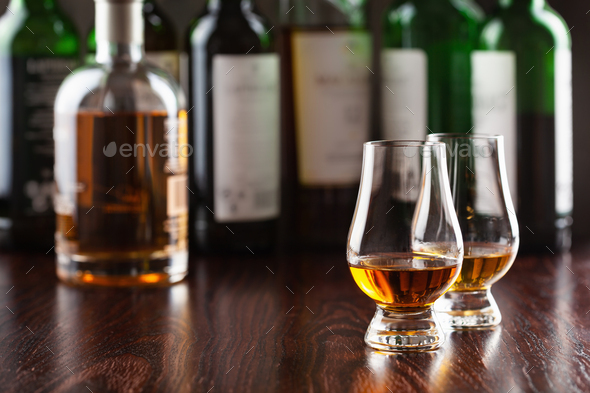 Bottles and glass of whisky spirit brandy on dark brown background - Stock Photo - Images