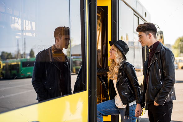 young couple in leather jackets holding hands and entering public transport - Stock Photo - Images