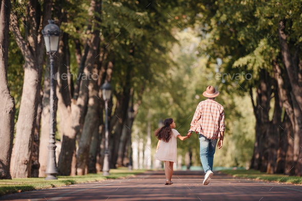 back view of african american girl holding hands with grandfather and walking in park - Stock Photo - Images