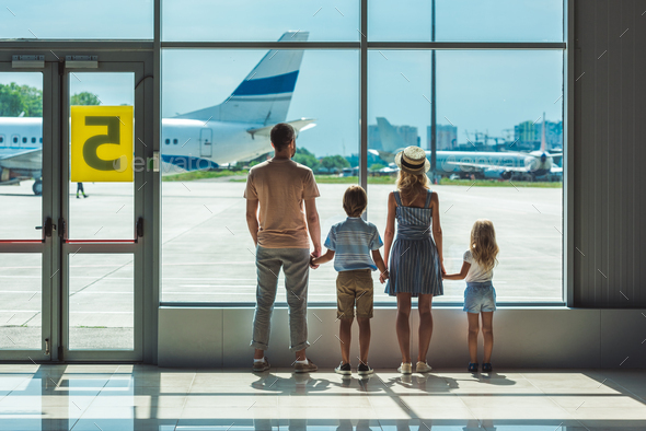 rear view of family looking out window together in airport - Stock Photo - Images