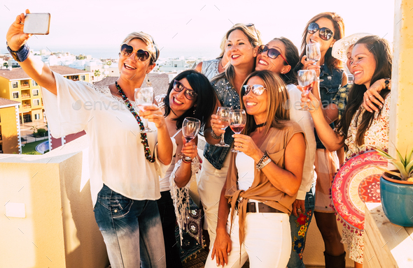 Group of people women enjoying party on the terrace celebrating and toasting with red wineglass - Stock Photo - Images