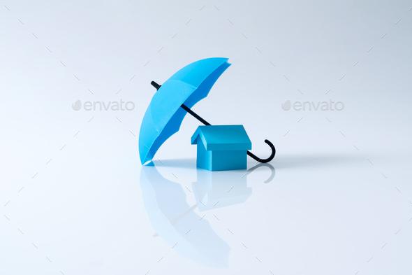House model under blue color umbrella - Stock Photo - Images