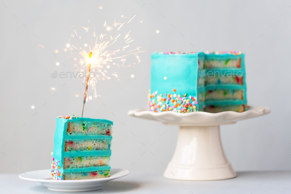 Birthday cake with colorful frosting and sparkler - Stock Photo - Images
