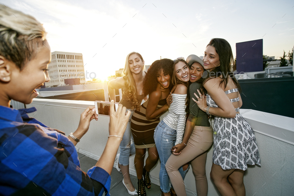 A group of young women partying on a city rooftop at dusk - Stock Photo - Images