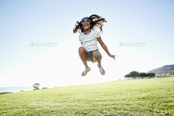 Young mixed race girl with long curly hair leaping in the air - Stock Photo - Images