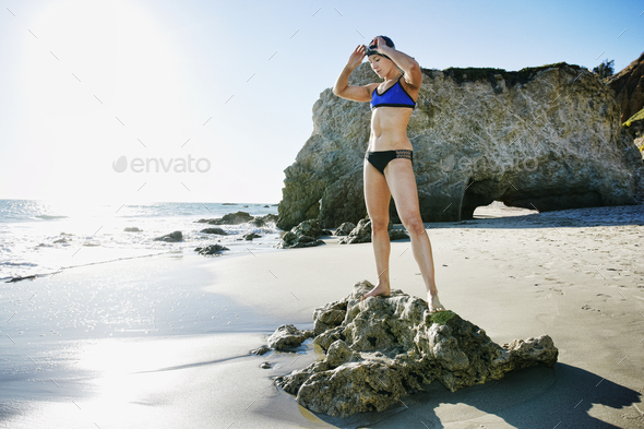 Young woman, triathlete in training in swimwear, swimhats and goggles on a beach. - Stock Photo - Images
