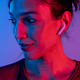 Attractive woman with earphones listening music in studio with blue and red lights - PhotoDune Item for Sale