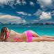 Woman wearing pink bikini laying on beach - PhotoDune Item for Sale