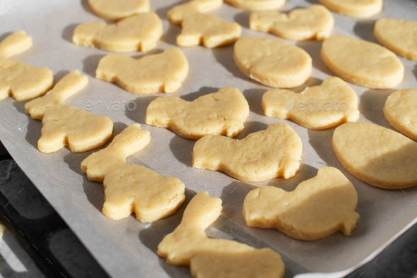 Ready for baking cookies cut in shape of rabbit, egg and chicken on parchment paper - Stock Photo - Images