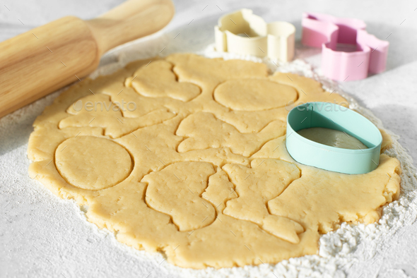 Dough with cookie cutters and rolling pin on kitchen table - Stock Photo - Images