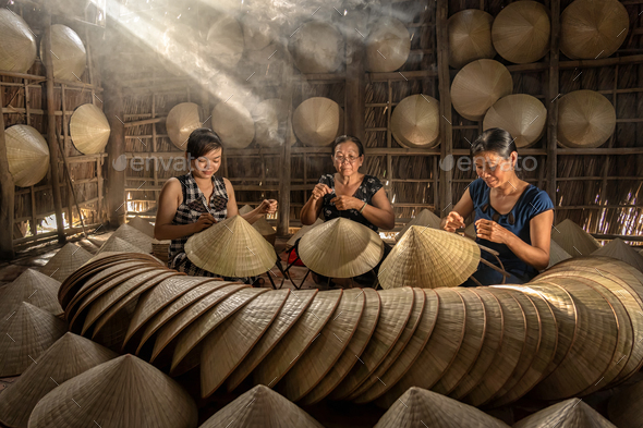Group of Vietnamese female craftsman making the traditional vietnam hat - Stock Photo - Images