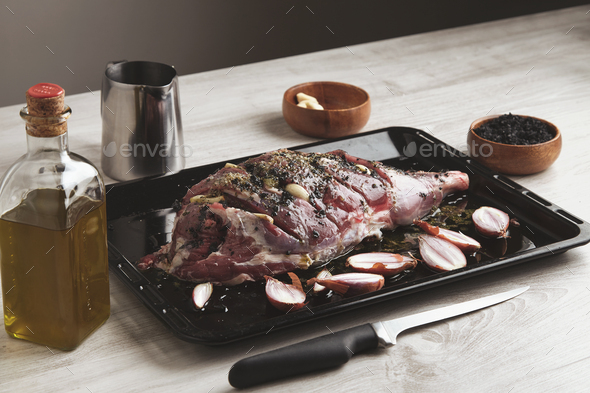 Pre cooked lamb leg on black roasting plate - Stock Photo - Images