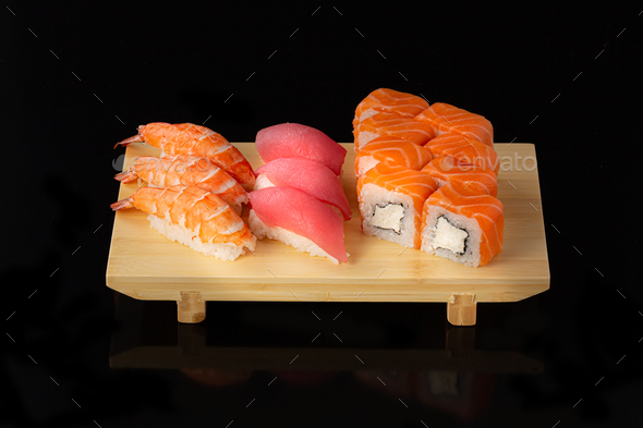Sushi set. Rolls with salmon eel red caviar and vegetables on black background - Stock Photo - Images