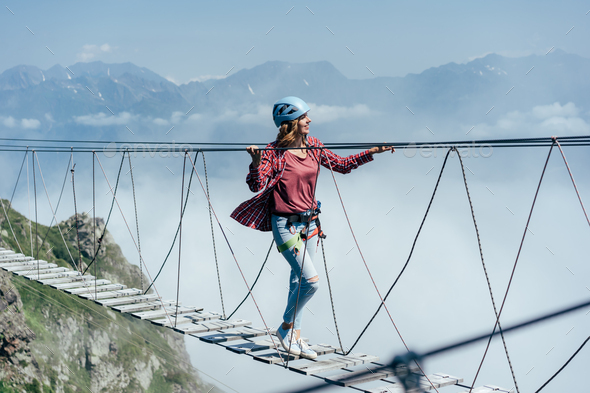 A happy cheerful woman walks on a suspension bridge high in the mountains. - Stock Photo - Images