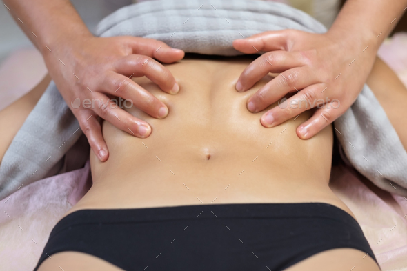 Caucasian young woman having stomach massage during spa treatment. - Stock Photo - Images